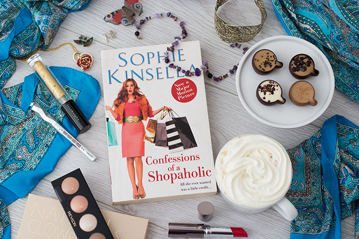 Confessions of a Shopaholic by Sophie Kinsella. Book around makeup, capuccino, jewellery, a scarf, chocolate cups.